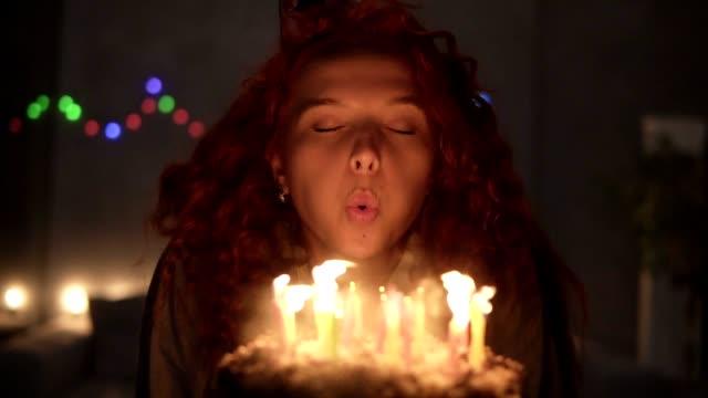 porträt eines lächelnden lockigen rothaarigen mädchens, das einen wunsch macht und kerzen auf ihrer geburtstagstorte ausbläst. gedämpftes licht, girlandenlichter. zeitlupe - geburtstagskerze stock-videos und b-roll-filmmaterial