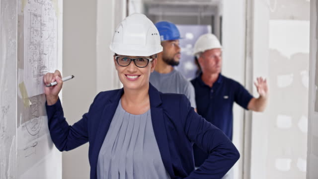 Portrait of a smiling female architect sketching on the board at the building site