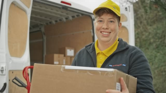 Portrait of a smiling female courier holding a package next to her van