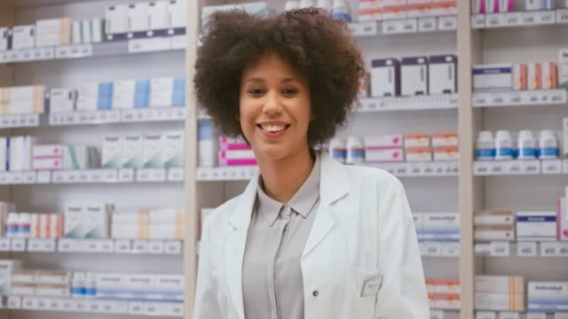 Portrait of a smiling female pharmacist standing behind the counter at the drugstore Wide handheld shot of a young biracial female pharmacist standing behind the counter at the drugstore and smiling into the camera. Shot in Slovenia. pharmacist stock videos & royalty-free footage