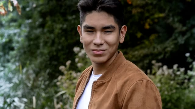 Portrait of a smiling  Latin American young man with a brown suede jacket, shot outside video