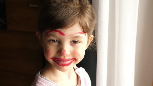 portrait of a smiling little girl with face painted with red lipstick