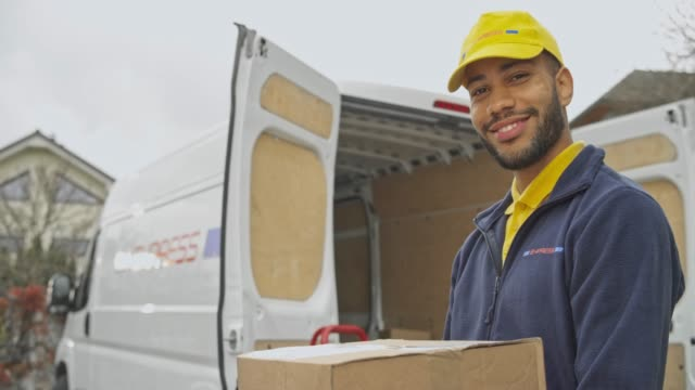 Portrait of a smiling male courier holding a package next to his van
