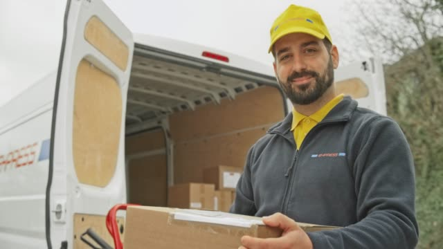 Portrait of a smiling male courier with a beard holding the package next to his van