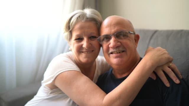 portrait of a smiling senior couple at home - 60 64 года стоковые видео и кадры b-roll