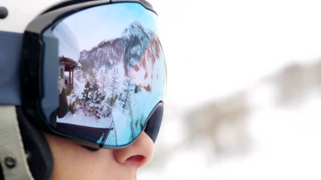 portrait of a smiling skier on vacation in the mountains, behind her you can see the snow-covered mountain. - sci video stock e b–roll