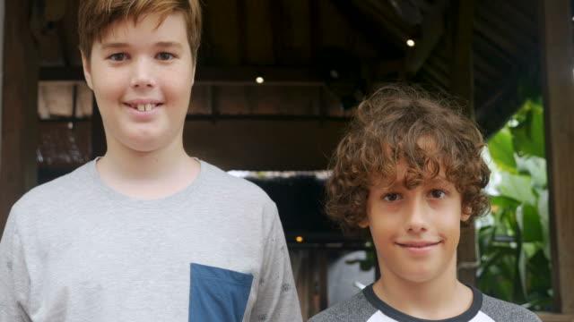 ritratto di un ragazzo alto e di un ragazzo corto sorridente e guardando la macchina fotografica - bassino video stock e b–roll