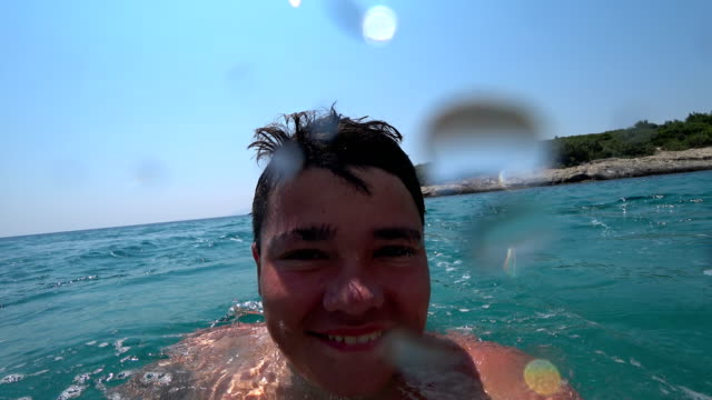 Portrait of a teenage boy jumping into a tropical sea from yacht