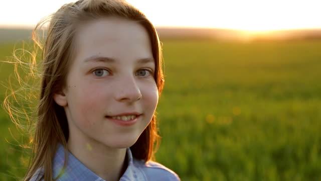 gün batımında bir alanda bir genç kız portresi - i̇nsan sırtı stok videoları ve detay görüntü çekimi