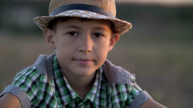 portrait eines jungen dorf in einen strohhut, blick in die kamera bei sonnenuntergang - strohhut stock-videos und b-roll-filmmaterial