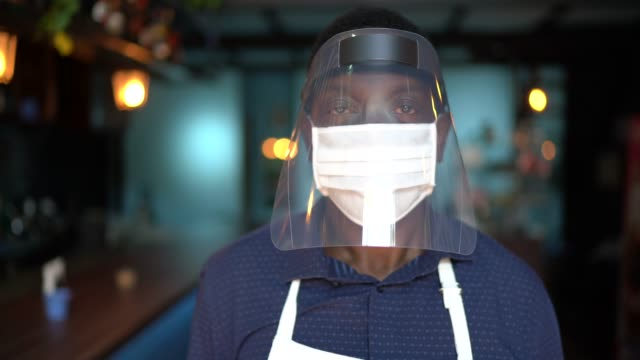Portrait of a waiter wearing protective face mask at restaurant Portrait of a waiter wearing protective face mask at restaurant shield stock videos & royalty-free footage