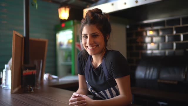 Portrait of a waitress behind the counter Portrait of a waitress behind the counter bent stock videos & royalty-free footage