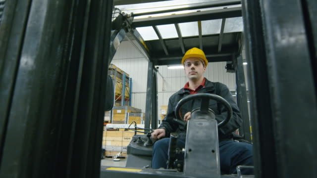 Portrait of a warehouse worker driving a forklift truck. Portrait of a warehouse worker driving a forklift truck. forklift stock videos & royalty-free footage