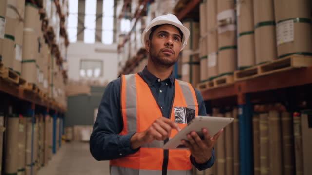 vídeos de stock e filmes b-roll de portrait of a warehouse worker using digital tablet while looking at warehouse storage area - armazém