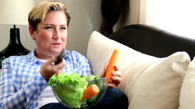 Portrait of a woman eating fresh diet food and watching tv at home