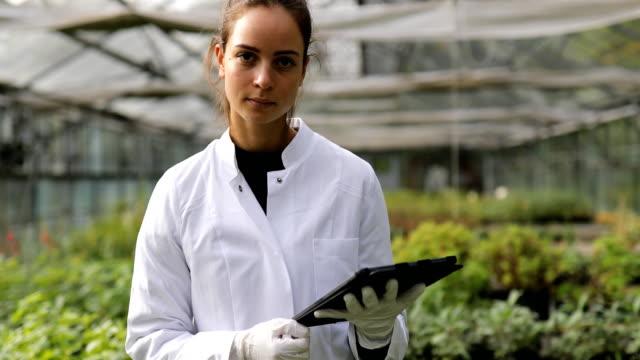 serada çiftçilik araştırmacısı bir kadın portresi - plant stem stok videoları ve detay görüntü çekimi
