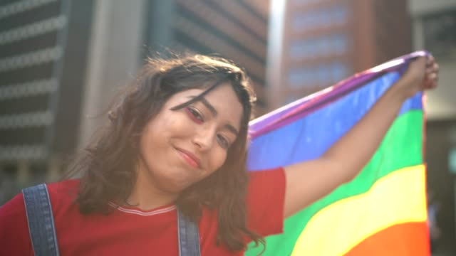 Portrait of a woman holding rainbow flag during LGBTQI parade Portrait of a woman holding rainbow flag during LGBTQI parade lgbtqi rights stock videos & royalty-free footage