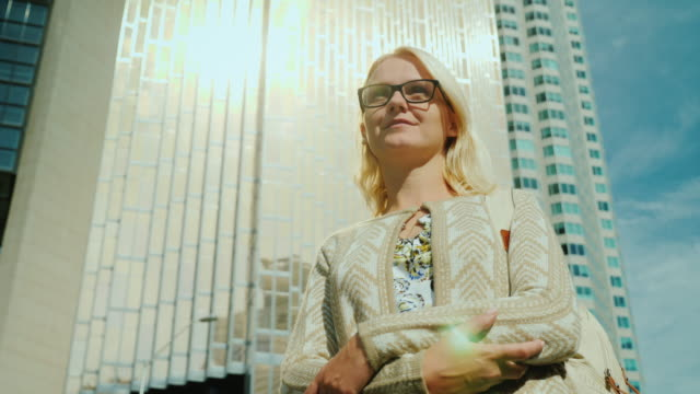 Portrait of a woman in a megacity. Admiration is looking around at the towering skyscrapers. The setting sun is reflected in the windows video