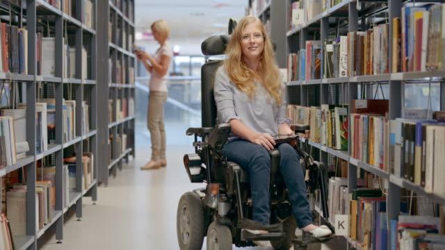 ld porträtt av en kvinna i rullstol leende i biblioteket gången - fysiskt funktionshinder bildbanksvideor och videomaterial från bakom kulisserna