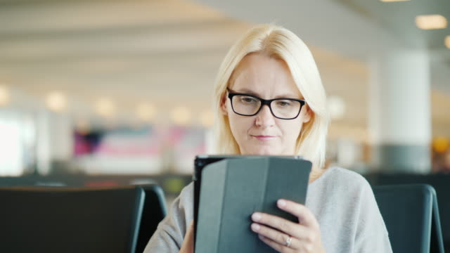 Portrait of a woman in glasses. Sits in the waiting room of the bus station, uses a tablet video