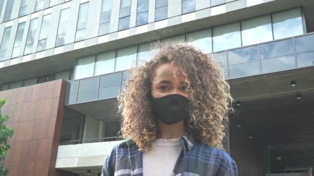 porträt einer frau auf der straße, die masken trägt und ihre freunde vor dem covid-19-virus sucht - lateinische schrift stock-videos und b-roll-filmmaterial