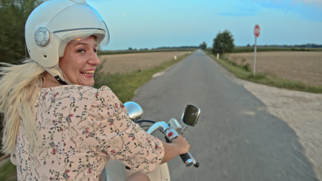 SLO MO Portrait of a woman riding a scooter on country road at dusk