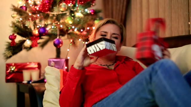Portrait of a  woman sitting near the christmas tree Christmas Gift -  Sad woman lying on a sofa near the christmas tree,  opening gift disappointed and unhappy, negative emotion stock videos & royalty-free footage