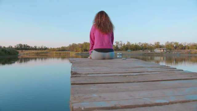 porträtt av en kvinna sitter på en träbrygga, titta på sjön känns gratis. koncept frihet, vacker sjöutsikt, glada människor, semester - flod vatten brygga bildbanksvideor och videomaterial från bakom kulisserna