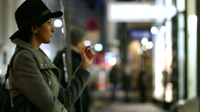 kulübün önünde sigara i̇çilmeyen bir kadın portresi - tütün mamulleri stok videoları ve detay görüntü çekimi
