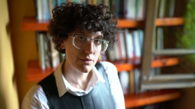 stockvideo's en b-roll-footage met portret van een vrouw die voor een bookshlef staat - mid volwassen vrouw
