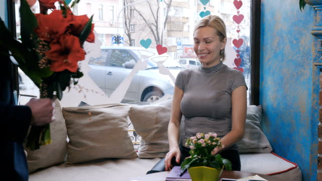 Portrait of a woman whose man gives a bouquet of flowers in a cafe video
