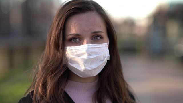 Porträtt av en kvinna med en ansiktsmask ser inte kameran video