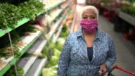 istock Portrait of a woman with disposable medical mask shopping in supermarket 1218024935