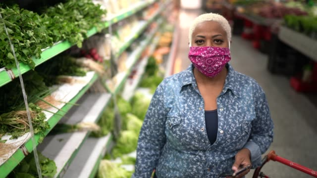 portrait of a woman with disposable medical mask shopping in supermarket - mask стоковые видео и кадры b-roll