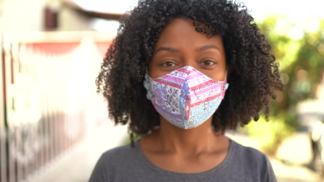 vídeos de stock e filmes b-roll de portrait of a woman with face mask at street - afro latino mask