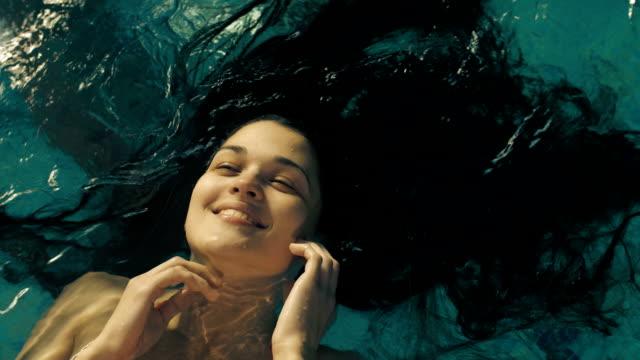 stockvideo's en b-roll-footage met portret van een vrouw met lang haar in water - hair woman