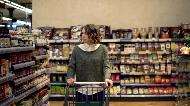 Portrait of a woman with wavy hair, wearing casual is driving shopping trolley through the row withfull of goods shelf in supermarket and looking around. Pretty girls, everyday life and buying products concept video