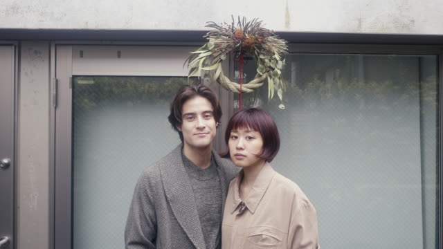 Portrait of a young adult couple under shime-kazari decoration on New Years Eve