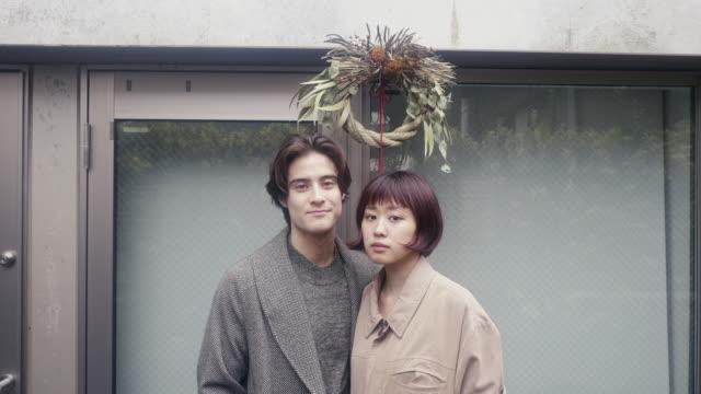 stockvideo's en b-roll-footage met portret van een jong volwassen paar onder shime-kazari decoratie op oudejaarsavond - 20 29 jaar