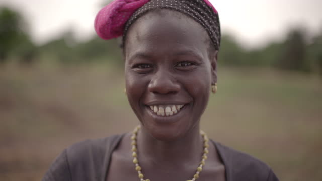 Portrait of a young African female farmer spontaneously laughing at camera