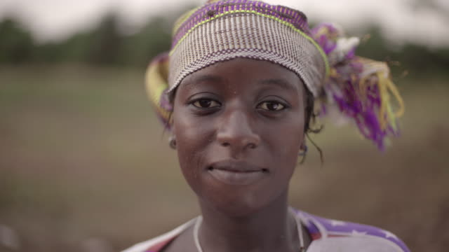 portrait of a young african female farmer spontaneously staring at camera - этническая группа стоковые видео и кадры b-roll