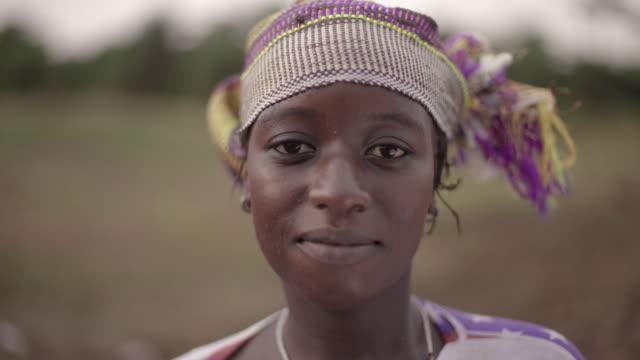 porträt eines jungen afrikanischen weiblichen landwirts spontan in die kamera starrt - stamm stock-videos und b-roll-filmmaterial