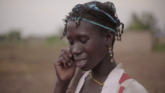 Portrait of a young African female farmer spontaneously talking on her cellphone video