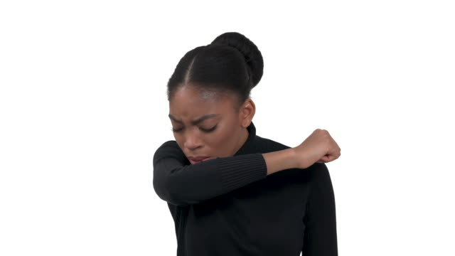 Portrait of a young african woman in a black roll-neck polo looking in to the camera and coughing or sneezing into elbow. Touching her neck. Having a heavy dry cough. Isolated on the white background