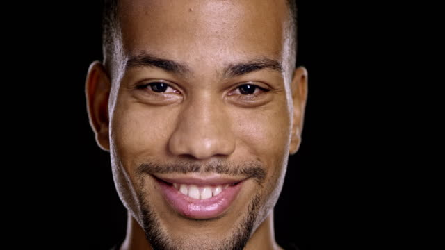 Portrait of a young African-American male smiling Close up shot of a young African-American male looking into the camera with a big smile on his face. Shot on black background. handsome people stock videos & royalty-free footage