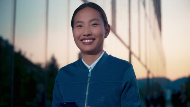 Portrait of a young Asian female entrepreneur typing on her smartphone outside a modern business building and smiling into the camera
