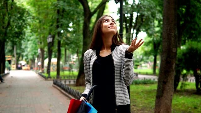 stockvideo's en b-roll-footage met portret van een jonge aantrekkelijke brunette vrouw met haar kleurrijke paraplu in haar handen als het regent in het stadspark te controleren. vervolgens is ze haar paraplu te openen. tikje schot - regen zon