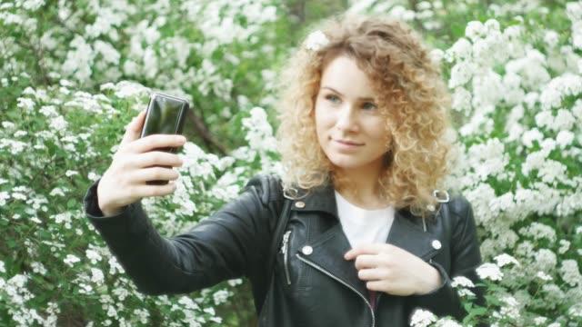 stockvideo's en b-roll-footage met portret van een jonge aantrekkelijke glimlachende kaukasische meisje staande in het park in overdag en met behulp van een smartphone, het maken van selfie, groene bush met witte bloemen op de achtergrond. zachte focus - blond curly hair