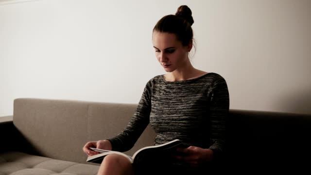 stockvideo's en b-roll-footage met portret van een jonge aantrekkelijke vrouw lezen van een tijdschrift zittend op de bank in haar woonkamer. vrijetijd - woman home magazine