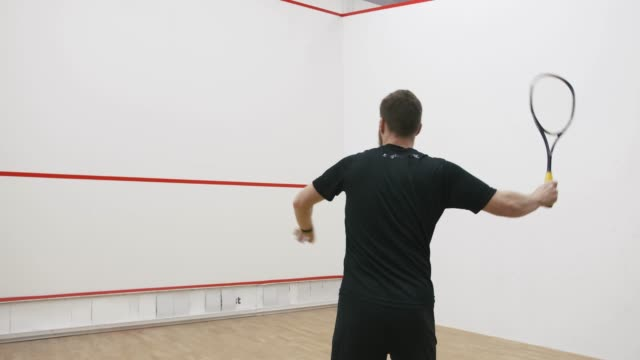 A portrait of a young bearded man practicing to play squash, slow motion